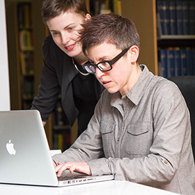 Photo of two lawyers working together in the library.